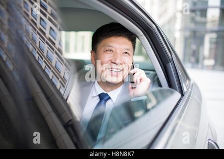 Zuversichtlich chinesischer Geschäftsmann reden über Handy im Auto - Stockfoto
