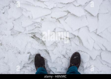Wanderstiefel am Fluss geknackt Schnee, Ansicht von oben. Konzept der Gefahr eine Ausfahrt nach schwachen Eis - Stockfoto