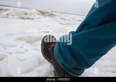 Männliche Füße auf die schwache schlechte River Ice Konzept Gefahr fallen durch das Eis. - Stockfoto