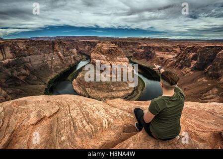 Horseshoe Bend, Colorado River und ein Wanderer am Rand sitzen und genießen Sie den Panoramablick. - Stockfoto