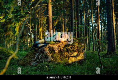 Mann schläft auf Moos bedeckt Felsen im Wald - Stockfoto