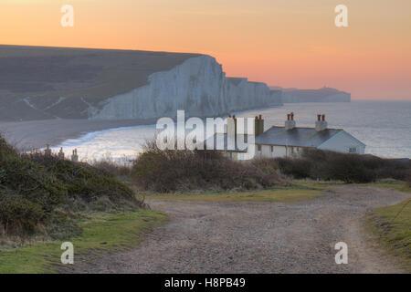 Die Seven Sisters Klippen und Küstenwache Hütten im Morgengrauen. Von Seaford Kopf, South Downs, East Sussex, England. - Stockfoto