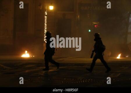 Athen, Griechenland. 15. November 2016. Polizisten marschieren vorbei ein brennendes Feuer-Bombe. Tausende von Demonstranten - Stockfoto
