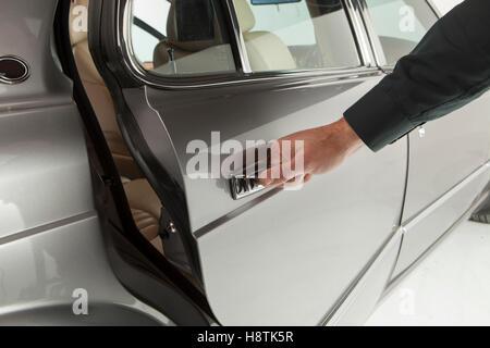 Mittleren Alter Geschäftsmann in klassischen Anzug öffnet sich ein Auto in einem motor Show Nahaufnahme - Stockfoto