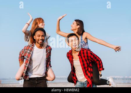 Zwei glückliche junge Paare geben hohe fünf und Spaß im freien