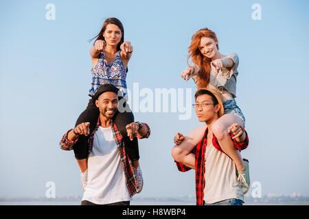 Zwei lächelnde junge Frauen sitzen auf den Schultern der ihre Freunde und zeigen Sie im freien - Stockfoto