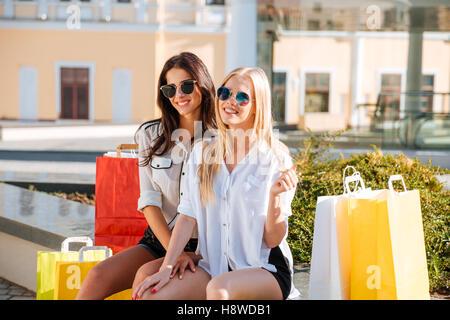 Zwei glückliche lächelnde Frauen sitzen auf Bank mit Einkaufstüten und Blick in die Kamera - Stockfoto