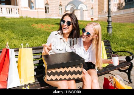 Zwei Frauen ruht auf einer Bank zusammen nach dem Einkauf - Stockfoto