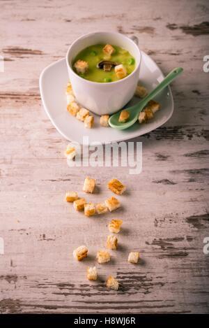 Vertikale Vintage retro-Foto von grüne Erbsensuppe in weißen Kaffeetasse mit Saucen und kleinen Brot gerösteten - Stockfoto