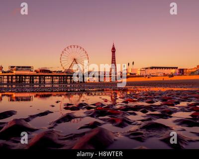 Blackpool Tower und Central Pier mit Spiegelung im Wasser am Strand bei Sonnenuntergang, Lancashire, UK. - Stockfoto