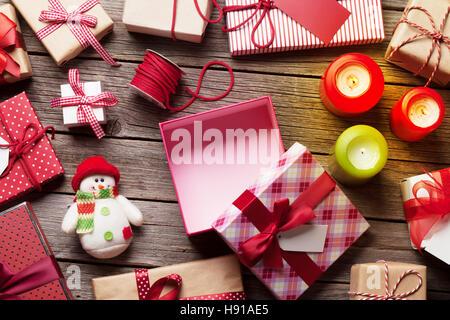 Weihnachts-Geschenk-Boxen und Kerzen auf Holztisch. Ansicht von oben. Geschenkverpackung Stockfoto