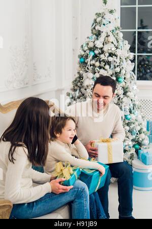 Glück, Generation, Reisen und Menschen Konzept - glückliche Familie mit Geschenk-Boxen auf Couch zu Hause - Stockfoto