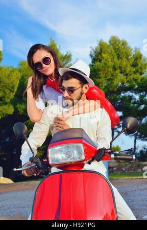 Schöne junge Paar in Liebe genießen und Spaß haben auf einem Roller fahren - Stockfoto