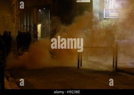 Athen, Griechenland. 17. November 2016. Eine Rauchbombe brennt hinter der Linie der Polizisten. Der Protestmarsch - Stockfoto