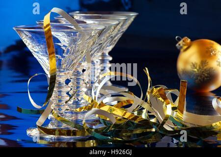 Reihe von cocktail-Gläser mit goldenen Weihnachtsdekoration vor blauem Hintergrund - Stockfoto