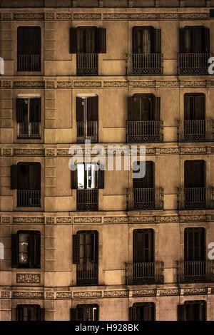 Eine einzelne Wohnung Licht leuchtet durch die dunkle Fassade der Gebäude der Innenstadt von. - Stockfoto