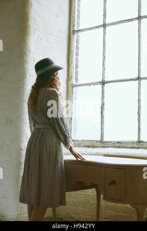 Frau in Vintage-Kleid und Hut stützte sich auf die Kommode und der Blick aus einem Fenster - Stockfoto