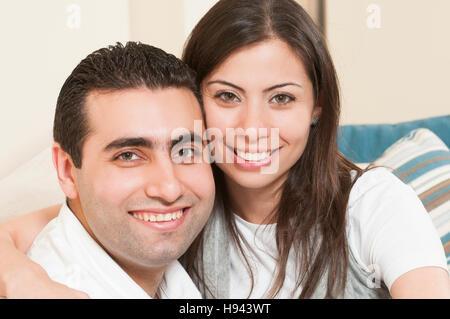 Glückliches Paar zusammen auf dem Sofa sitzen - Stockfoto