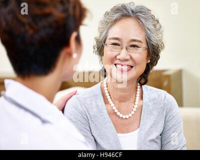 Senior asiatische Frau, die ein angenehmes Gespräch mit ihrem Hausarzt, glücklich und lächelnd - Stockfoto