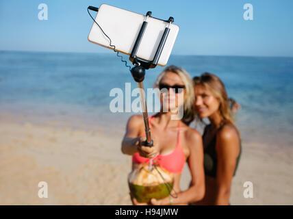 Zwei junge Freundinnen am Strand unter Selbstbildnis mit Handy auf Selfie Stick. Frauen am Strandurlaub nehmen Selfie. - Stockfoto