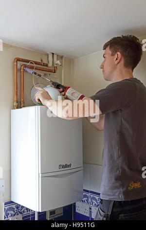 Ein junger Klempner verwendet eine Lötlampe Wasserpfeife Verbindungen zu einem neu installierten inländischen Kessel - Stockfoto
