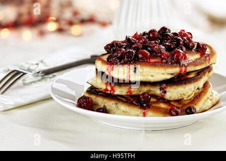 Cranberry-Sauce mit Ahornsirup, Butter und frische Cranberries über leckere goldene Pfannkuchen für Weihnachtsmorgen. - Stockfoto