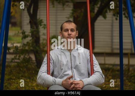 Mann sitzt auf einer Schaukel - Stockfoto
