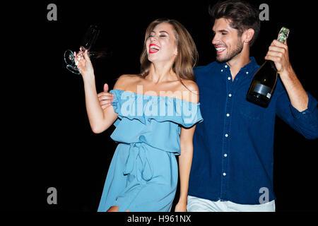 Glückliches junges Paar mit Gläser und Flasche Sekt am Strand in der Nacht - Stockfoto