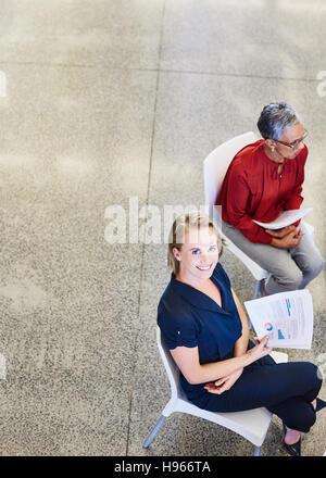 Porträt lächelnd Geschäftsfrau mit Papierkram im meeting - Stockfoto