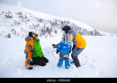 Familie mit Selfie Stick auf verschneiten Bergen - Stockfoto