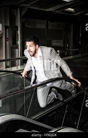 Geschäftsmann in Panik. Starker junger Mann auf Rolltreppe. Stress-Konzept. - Stockfoto