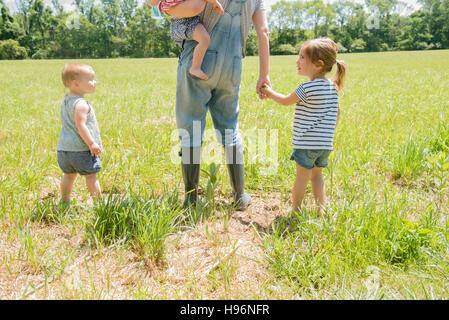 USA, Pennsylvania, Washington Crossing, Mutter mit drei Töchtern (18-23 Monate, 2-3) zu Fuß auf der grünen Wiese - Stockfoto