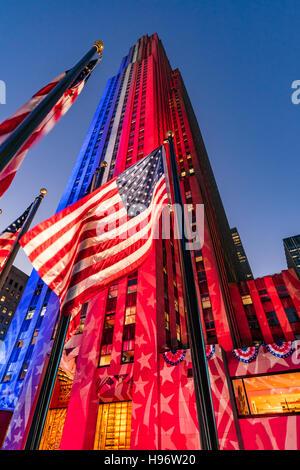 Rockefeller Center in der Dämmerung in weiß, rot und blau beleuchtet. Amerikanische Flaggen flattern im Wind. Midtown - Stockfoto