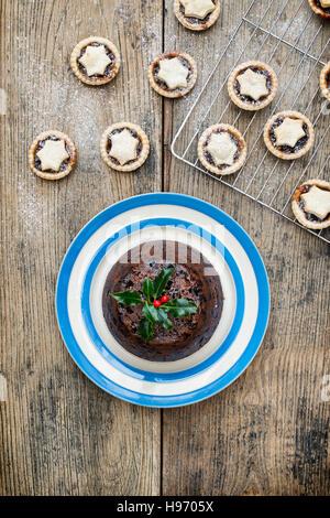 Christmas Pudding auf einem Teller von oben mit Mince pies - Stockfoto