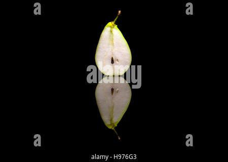 Halbieren Sie eine Birne auf schwarzen reflektierenden Hintergrund isoliert