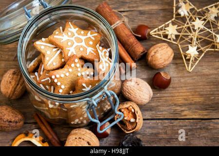 Lebkuchen-Christmas Cookies Sterne in das Glasgefäß mit weihnachtlichen Gewürzen und Dekor hautnah - Stockfoto