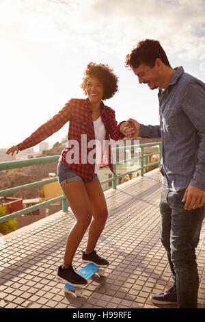 Junger Mann Lehre Mädchen um skateboard und hielt ihre Hand fest in großer Konzentration, während sie ihren anderen - Stockfoto