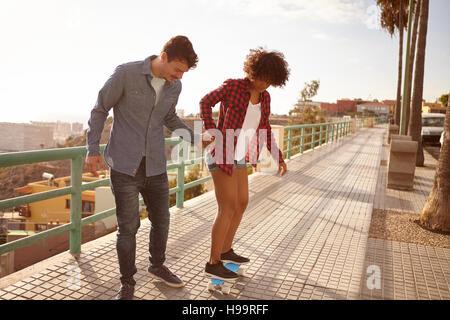 Junger Mann lehrt Mädchen Skateboard und hielt ihre Hand fest in großer Konzentration, während sie nach unten zu - Stockfoto