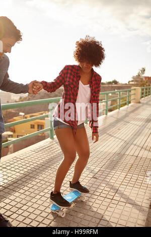 Junger Mann Lehre lockiges Mädchenakt um skateboard und hielt ihre Hand fest in großer Konzentration, während sie - Stockfoto