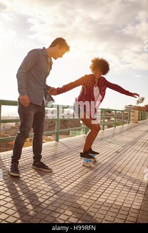 Lockige Mädchenakt mit gedrückter junge Skateboard lernen hält ihre Hand fest in großer Konzentration während sie - Stockfoto
