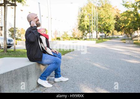 Vater mit Babymädchen in Babytrage mit Telefon - Stockfoto