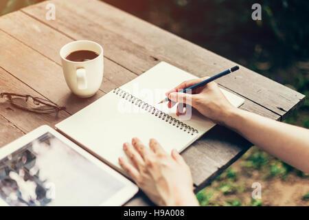 Weibliche Hand mit Bleistift schreiben auf Notebook. Frau Hand mit Bleistift schreiben auf Notebook im Coffee Shop. - Stockfoto