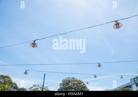 Eine abstrakte Schuss von Straßenlaternen aufgehängt Drähte vor blauem Himmel - Stockfoto