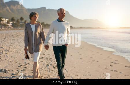Schuss von älteres paar Strand zusammen Hand in Hand entlang spazieren. - Stockfoto