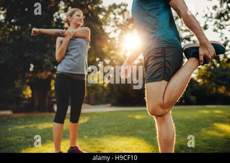 Aufnahme des jungen Mann und Frau im Park ausdehnen. Junges Paar morgens Aufwärmen. - Stockfoto