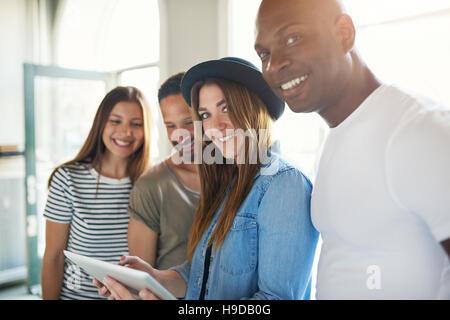Junge trendige lächelnd Gruppe von vier Freunden mit Tablet Spaß und Blick in die Kamera im Sonnenlicht. - Stockfoto