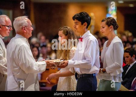 Teenage Ministranten in einer katholischen Kirche in Laguna Niguel, CA, bringen gefüllte Sammlung Körbe zu einem - Stockfoto