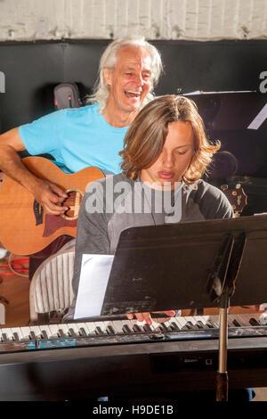 Eine begeisterte Gitarrist begleitet ein teenboy auf Tastatur an einem Vorsprechen für eine lokale Konzert in Huntington - Stockfoto