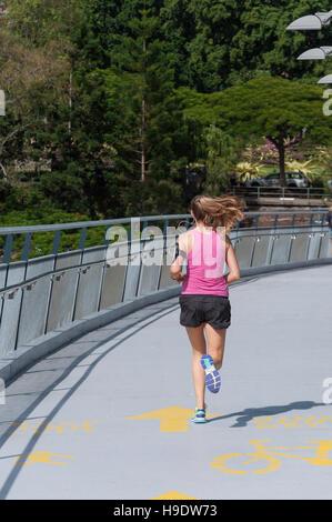Junge weibliche Läufer Kurilpa Brücke über den Brisbane River in Brisbane City, Brisbane, Queensland, Australien - Stockfoto