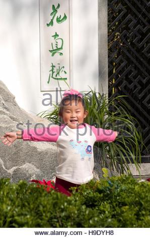 Eine junge Chinesin spielen in einem Garten im Bereich Serviceleistungen von Peking, China. - Stockfoto